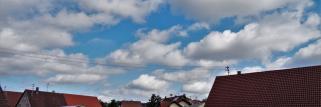 heubergwetter:  sonne und wattebäusche, auf blauem hintergrund.